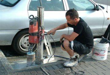 עובד חברת שחר צדיק בעבודת קידוח רצפת בטון