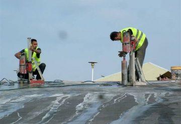 עובדי חברת שחר צדיק בעבודת קידוח בגג בטון