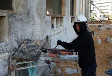 עובד בעבודת קידוח בקיר בטון באתר בנייה