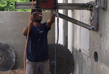עובד חברת שחר צדיק בעבודת קידוח בקיר בטון