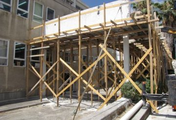 ניסור חומת בטון הנתמכת על ידי פיגומי עץ