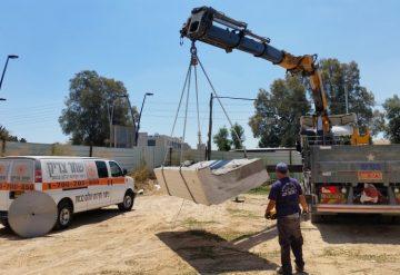 יחידת בטון לאחר ניסור תלויה על מנוף לצד רכב עבודה של החברה