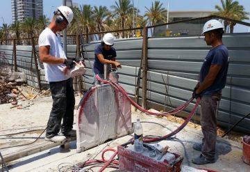 שלושה עובדים בניסור משטח בטון עם מסור ייעודי