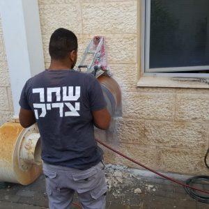 עובד של חברת שחר צדיק מבצע קידוח בקיר בטון