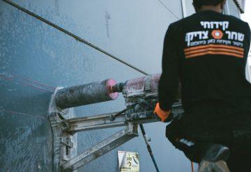עובד חברת שחר צדיק בזמן קידוח בקיר בטון