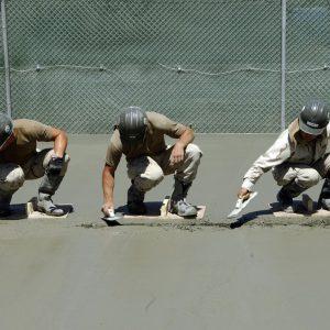 שלושה עובדים עושים שפכטל לרצפת בטון