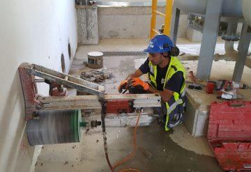 עובד של שחר צדיק מבצע קידוחים בקיר בטון